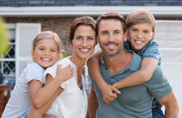A young family smiles happily together.