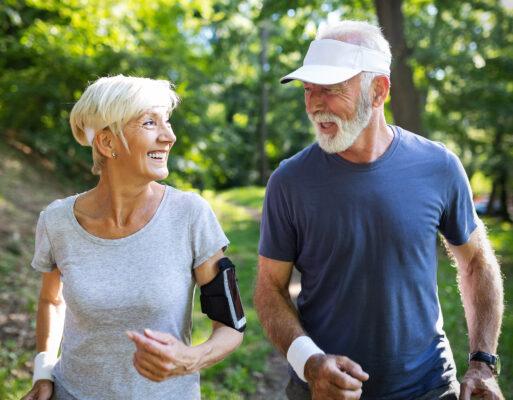 An active couple in their seventies takes an exercise walk through a park.
