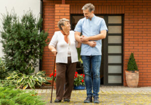 Man assisting elderly woman